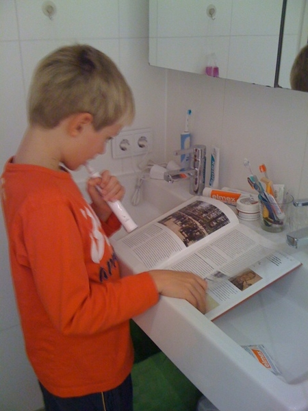 Multi tasking son: toothbrushing while reading!