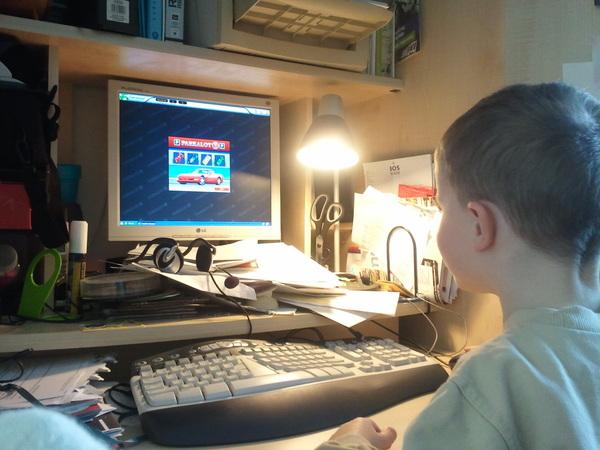 Arjen speelt op de computer. (En ja, ik moet die zooi eens opruimen...)