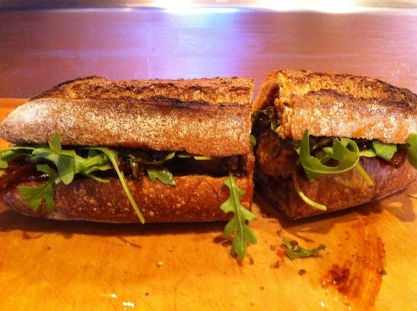 Epifanio just took this torta out of wood burning oven.Red chile rst chicken,pickled white onions,arugula,bl beans